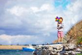 Bambino felice con standing girandola sulla scogliera vicino al mare — Foto Stock