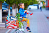 Kid in trolley full of foodstuffs after shopping — Stock Photo