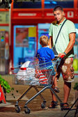 Father and son with trolley after shopping — Stok fotoğraf