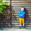 Cute fashionable boy in front of wooden wall — Stock Photo