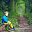 Sad kid sitting on rails in green tonel — Photo