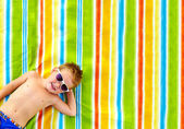 Happy kid sunbathing on colorful blanket — Stock Photo