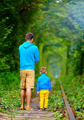 Father and son walking on rails in green tonel — Stock Photo