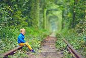 Garoto bonito sentado sobre carris no tonel verde — Fotografia Stock