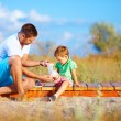 Father bandaging injured leg of kid — Stock Photo