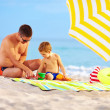 Happy father and child playing in sand on the beach — Stock Photo