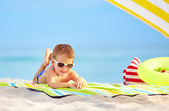Cute kid in sunglasses resting on colorful beach — Stock Photo