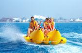 Gens heureux s'amuser sur le bateau de banane — Photo