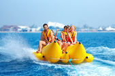 Happy people having fun on banana boat — Stock Photo