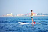 Young man standing on paddle board in the sea — Stock Photo