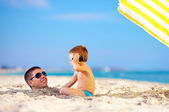 Happy kid talking on the phone, father head in sand — Stock Photo