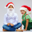 Stock Photo: Cute santa claus and little helper on white