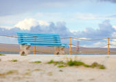 Old blue bench on cloudy background — Stock Photo