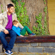 Stylish father and son on the bench, in front of old tree — Foto de Stock