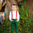 Cute boy posing in front of old tree — Stockfoto