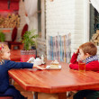 Cute kids sitting in cafe — Stock Photo