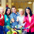 Stock Photo: Group of happy people in supermarket, thumb up