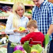 Candid portrait of family buying food in supermarket — Stock Photo