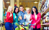 Group of happy people in supermarket, thumb up — Stock Photo