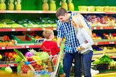 Candido ritratto della famiglia di acquistare cibo in un supermercato — Foto Stock