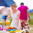 Happy girl preparing food on picnic table — Stock Photo