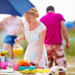 Happy girl preparing food on picnic table — Stock Photo #34654325