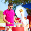 Happy man prepares food on the grill, family picnic — Stock Photo