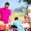 Happy man cooks vegetables on the grill, family picnic — Foto de Stock