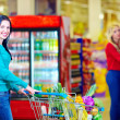 Smiling woman shopping at supermarket with trolley — Stock Photo