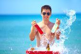 счастливый человек с напитками и плеск воды на пляжную вечеринку — Стоковое фото