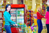 Smiling woman shopping at supermarket with trolley — Stok fotoğraf