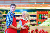 Smiling grocery staff working in supermarket — Stock Photo