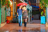 Happy couple walking under the rain on cozy colorful street — Stock Photo