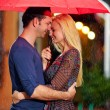 Happy couple under the rain on evening street — Stock Photo