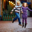 Stock Photo: Happy kids jumping under the rain
