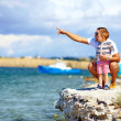 Happy father and son on the cliff near the lake — Stock Photo