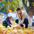 Happy father and son having fun in autumn park — Stockfoto