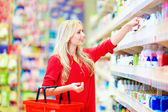 Beautiful woman choosing personal care product in supermarket — Stock Photo
