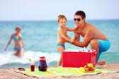 Happy family on summer beach picnic — Stock Photo