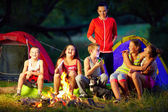 Happy kids telling interesting stories around campfire — Stock Photo