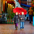 Cute children walking colorful evening street, under the rain — Stock Photo #35152313