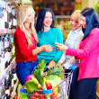 Group of beautiful girls choosing wine in supermarket — Stock Photo
