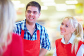 Polite supermarket staff serves customer — Stock Photo