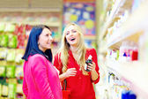 Beautiful women choose personal care product in supermarket — Stock Photo