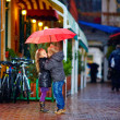 Young couple kissing under the umbrella on the street — Stock Photo