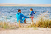 Father and son together on lake coast — Stock Photo