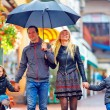Happy family walking under the rain on colorful street — Stock Photo