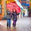 Happy kids walking under the rain on colorful street — Foto de Stock