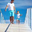 Happy father and son walking on blue sky horizon — Stock Photo