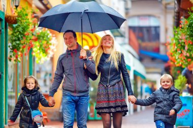 Happy family walking under the rain on colorful street